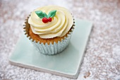 A cupcake decorated with light frosting and marzipan leaves