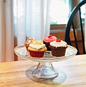 Four Assorted Homemade Cupcakes on a Pedestal Dish