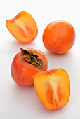 Whole and halved persimmons