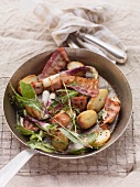 Fried potatoes with root vegetables, spring onions, bacon and herbs