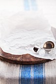 Baking paper, glass bowls and a silver spoon on a wooden bread