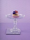 A raspberry cupcake on a cake stand