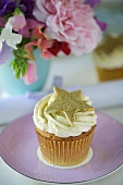 A cupcake decorated with a golden star