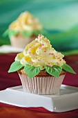 A cupcake with yellow frosting and marzipan leaves