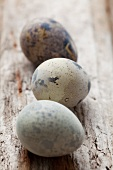 A quail's egg on a wooden surface
