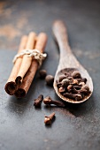 Cinnamon, cloves and allspice berries on a rustic surface