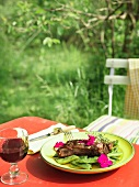 Steak with green beans and edible flowers in a garden