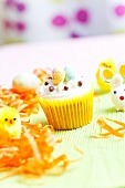 A cupcake with vanilla frosting and sugar eggs for Easter