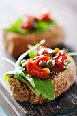 Crostini campagnoli (toasted bread topped with tomatoes, capers and rocket)