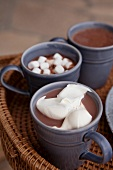 Cups of cocoa with cream and marshmallows