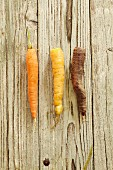 Three different carrots on a wooden surface