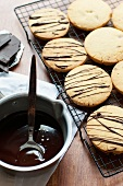 Shortbread cookies drizzled with chocolate on a wire rack
