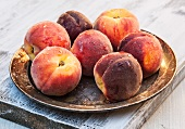 Fresh peaches on a metal plate