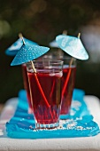 Red summer drinks with blue umbrellas