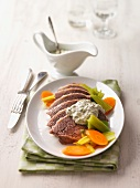 Cooked beef with green sauce and vegetables