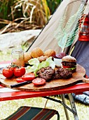 Home-made mini burgers on a camping table outdoors