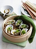 Steamed oysters in a bamboo steamer