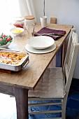 Pikanter Auflauf, Salat und Einzelgedeck aus weißem geschirr auf schlichtem Holztisch mit Küchenstuhl
