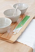 Pale grey clay bowls and chopsticks wrapped in paper on wooden board