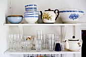 Crockery and glasses on bracket shelves in corner of simple room