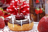 A doughnut with cherries and chocolate glaze