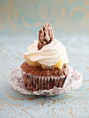 A cupcake garnished with spiced pears and cream
