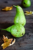 Green pears and autumnal leaves on a wooden surface