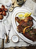 Barbecued T-bone steak with herb oil and onions cooked with Taleggio cheese
