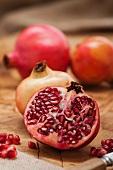 Granatäpfel, ganz, halbiert, und Granatapfelkerne