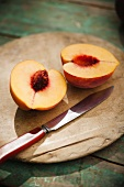 Halved Peach on a Cutting Board with a Knife