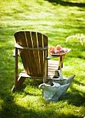 Deckchair mit Pfirsichen auf der Armlehne, daneben zwei alte Giesskannen