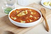 Bowl of Tomato Artichoke Soup; Wooden Spoon