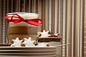 Cinnamon stars and chocolate covered marzipan with a latte macchiato with a red bow