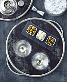 A Tray with Two Martinis and Three Bowls of Assorted Olives and Onions; From Above