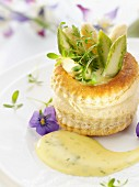A vol-au-vent with asparagus tips and herby hollandaise sauce