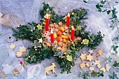A Christmas wreath with candles made of box hedge, holy, ivy and Christmas roses filled with Christmas biscuits and marzipan fruits
