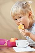 A little girl eating cake dunked in milk