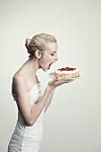 A young woman about to bite into a strawberry cake