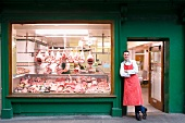 Butcher leaning against butcher shop doorway