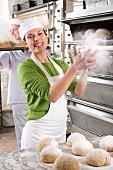 Baker sprinkling bread loves with flour