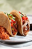 Two Taco; Both Have a Soft Shell Layered Inside a Hard Shell; One with Beef Filling; One with Chicken Filling; Rice