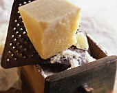 A chunk of Parmesan on a rusty cheese grater