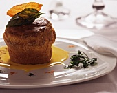 A cheese soufflé with fontina cheese sauce and caramelised herbs