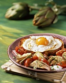 A fried egg on toast with grilled tomatoes and artichokes