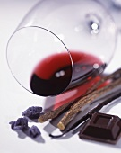 A glass of red wine lying on its side, with candied violets, dark chocolate, a vanilla pod and liquorice roots