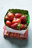 Strawberries and tomatoes in a small box