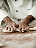 A chef rolling out gnocchi dough on a floured work surface