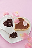 A heart-shaped mini chocolate torte with pink rose petals