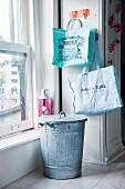 Zinkeimer mit Deckel und bedruckte Taschen in Küche neben Schiebefenster