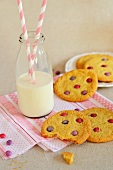 Sable biscuits with coloured chocolate beans, and a milk bottle with drinking straws